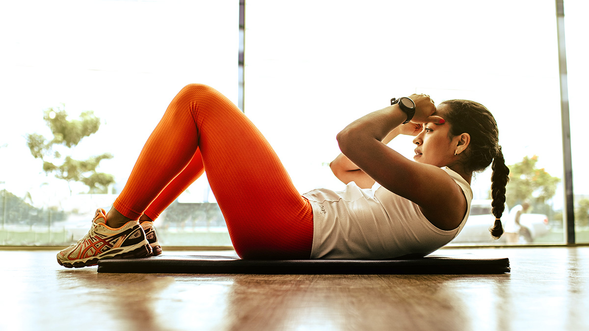 Woman doing a sit-up at home on yoga mat